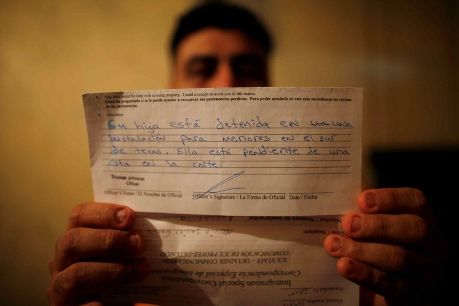 A man holds a letter written in Spanish that tells him his daughter is in a detention center awaiting a trial.