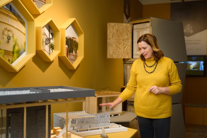 A woman stands over a small model of a beehive. Behind her is a yellow wall with honey-comb shaped pictures.