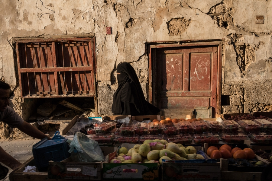 A woman passes a cart carrying produce in Al-Balad, Jeddah.