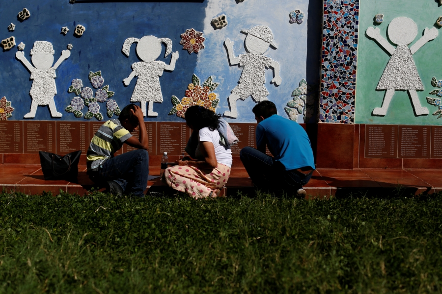 three people kneel near a wall with silhouettes of children