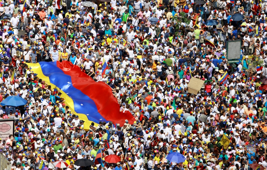 A massive crowd holds a large Venezuelan flag as they take part in a rally