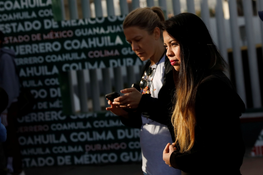 Two women wait at the Chaparral border crossing in Tijuana, Mexico.