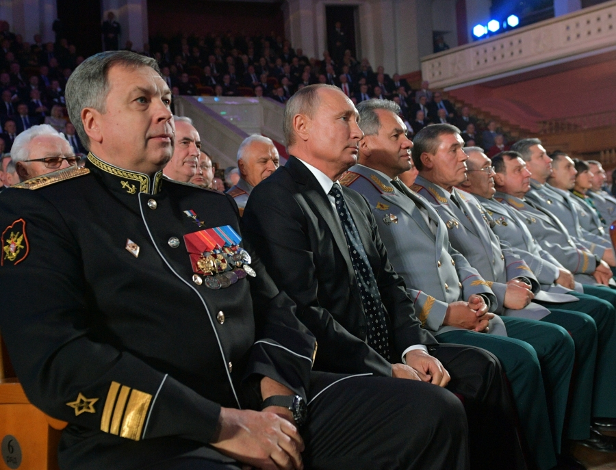 Russia's President Putin sits next to several military members