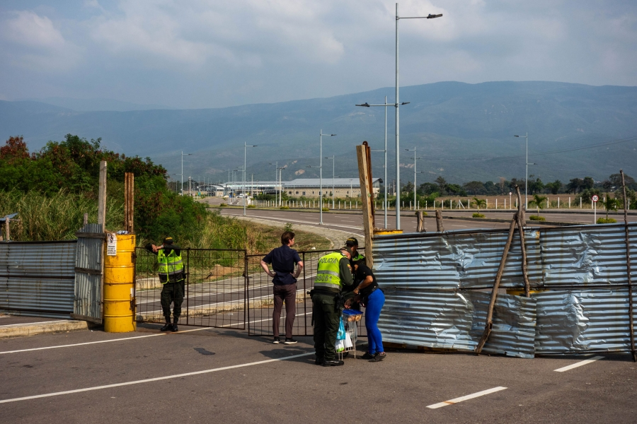 Police stand near a barricaded bridge.