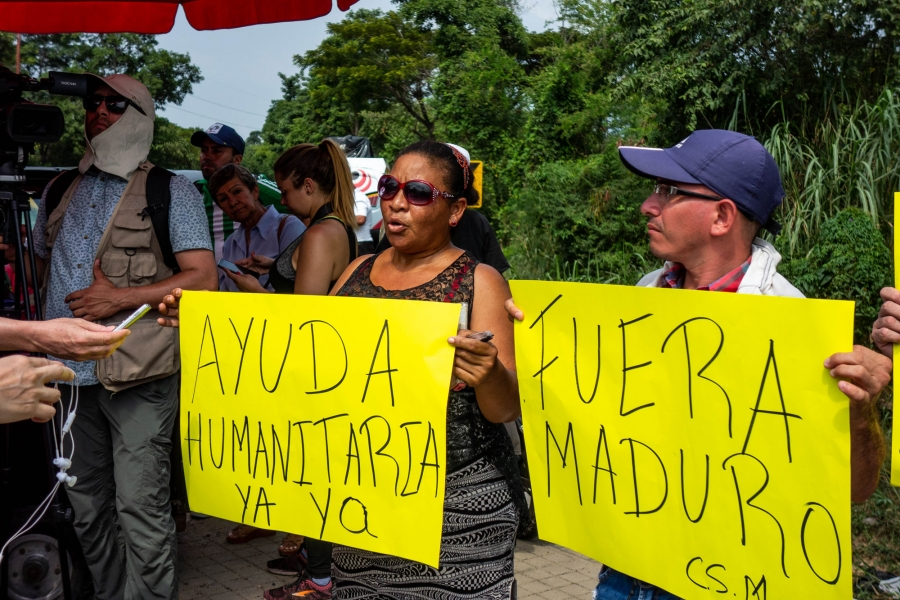 Protesters hold yellow signs with Spanish words.