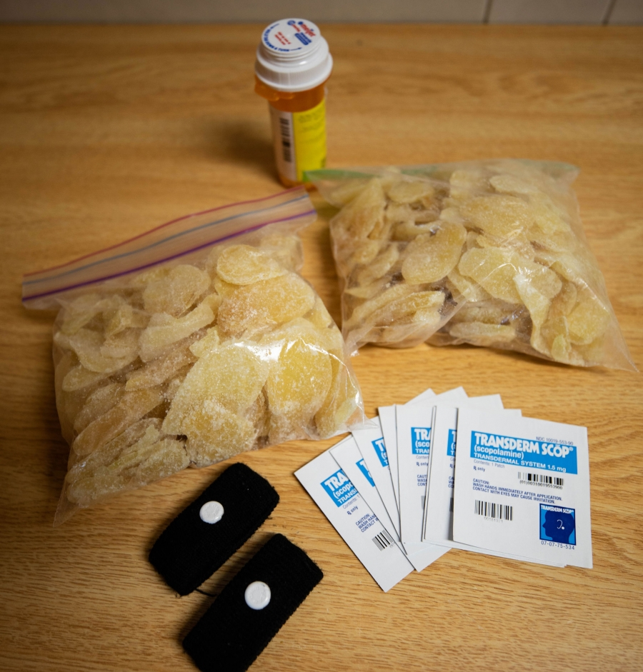 Seasickness patches, acupressure wristbands and crystallized ginger are shown on a table.