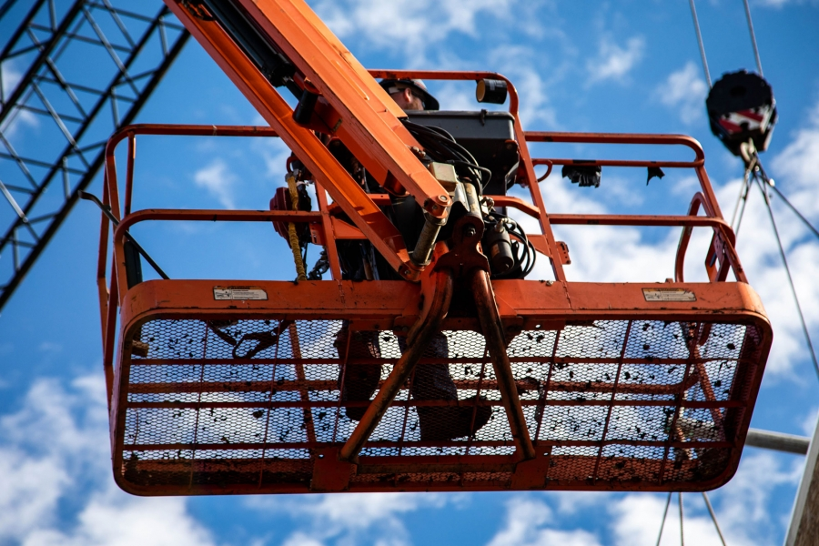 A worker is shown from below standing on an orange platform of a hydraulic crane.