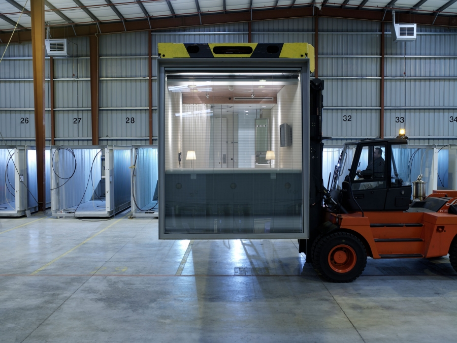 A modular apartment unit from CitizenM is shown on a factory floor being moved using a forklift.