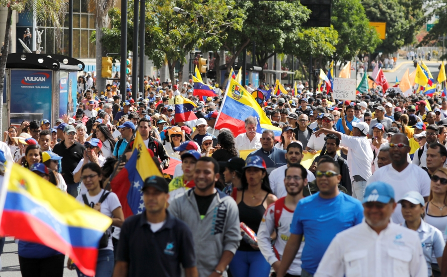 Opposition supporters are shown en masse in the street with placards and Venezuelan flags.