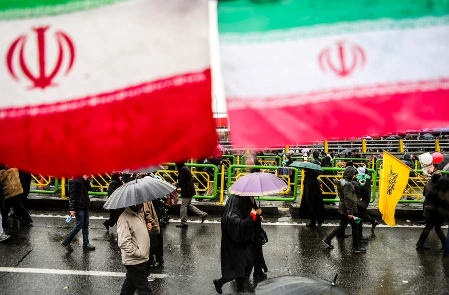 Iranian people carry umbrellas under giant Iranian flags