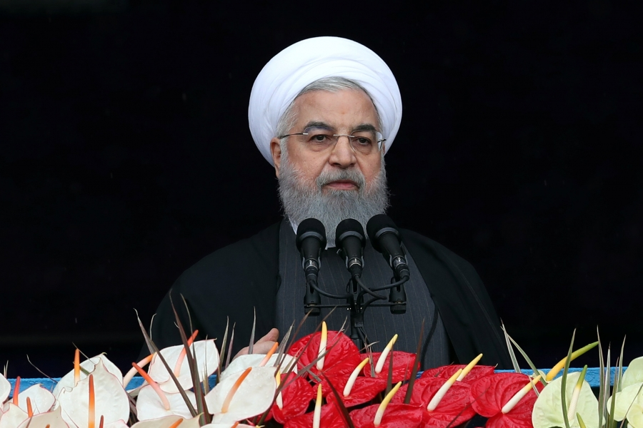 Iran's President Hassan Rouhani speaks behind a podium covered in red and white flowers