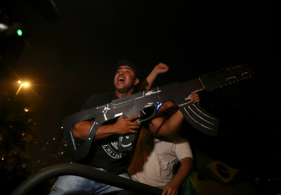 a man wearing a dark t-shirt holds a large cardboard gun
