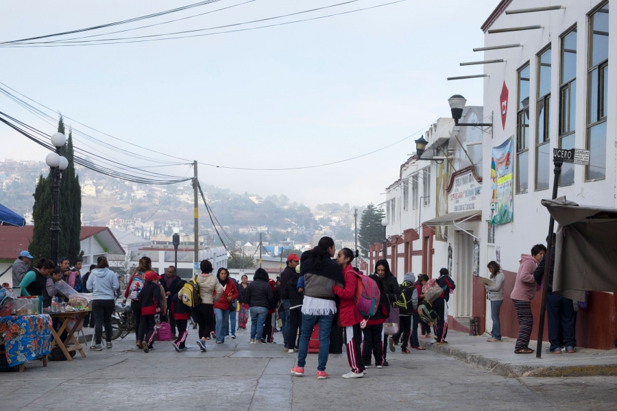 A group of people are shown outside of Tlaxiaco's elementary school during morning drop-off.
