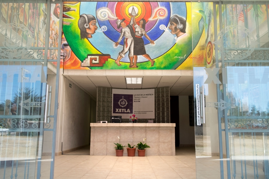 The lobby at XETLA is shown with a desk center frame under a colorful mural.