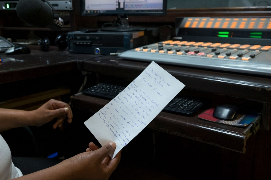 A close-up photo shows Eva Hernández holding a hand-written note by listener Floriana Espinoza.