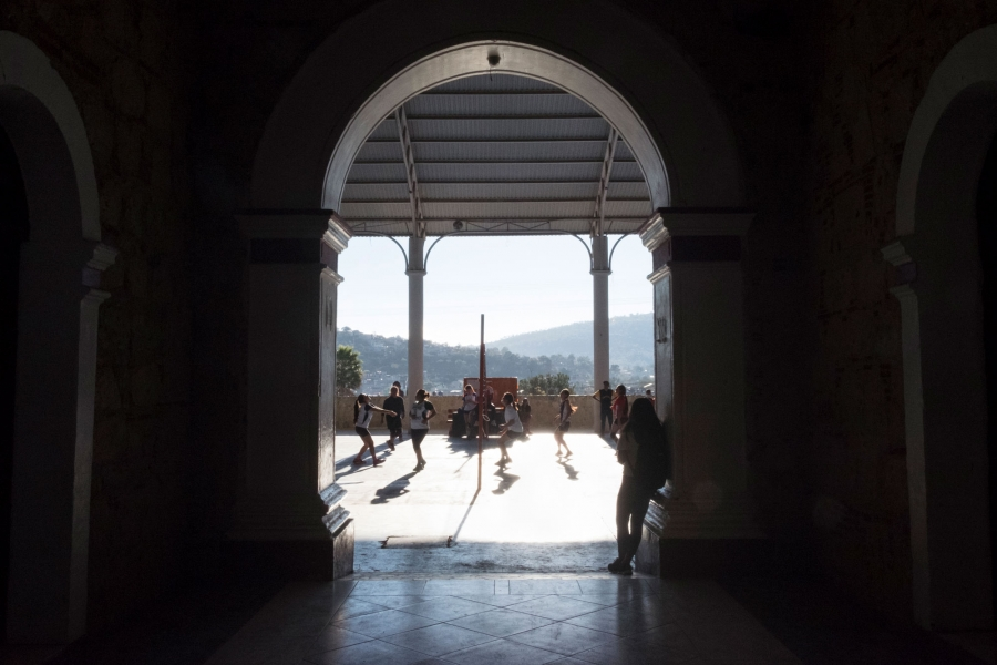 Women are shown playing volleyball in the distance.