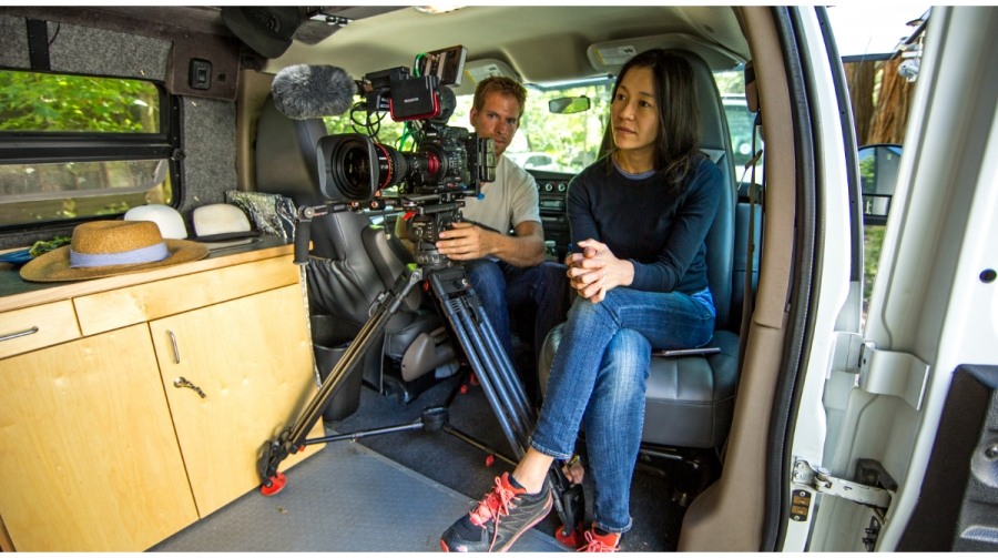 Chai Vasarhelyi seats inside a van with a cameraman and his camera.