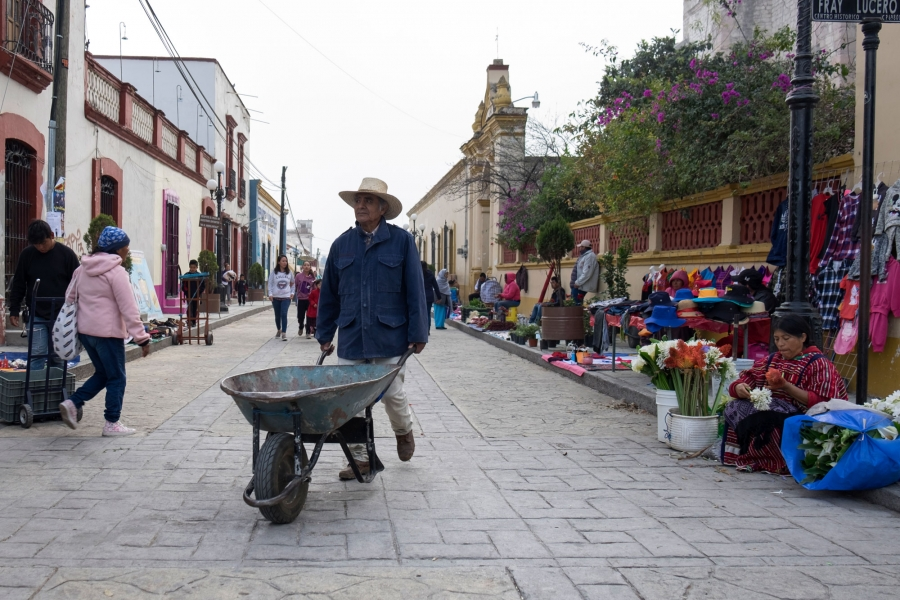 People head to work in the early morning hours in Tlaxiaco including a man pushing a wheelbarrow in the nearground.