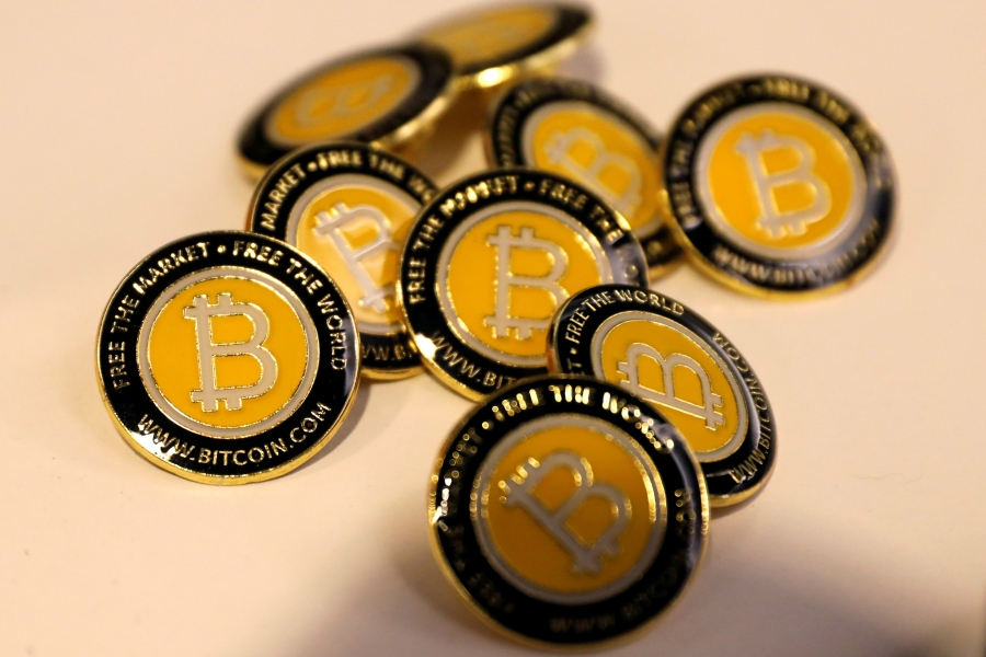 about a dozen bitcoin buttons in a pile