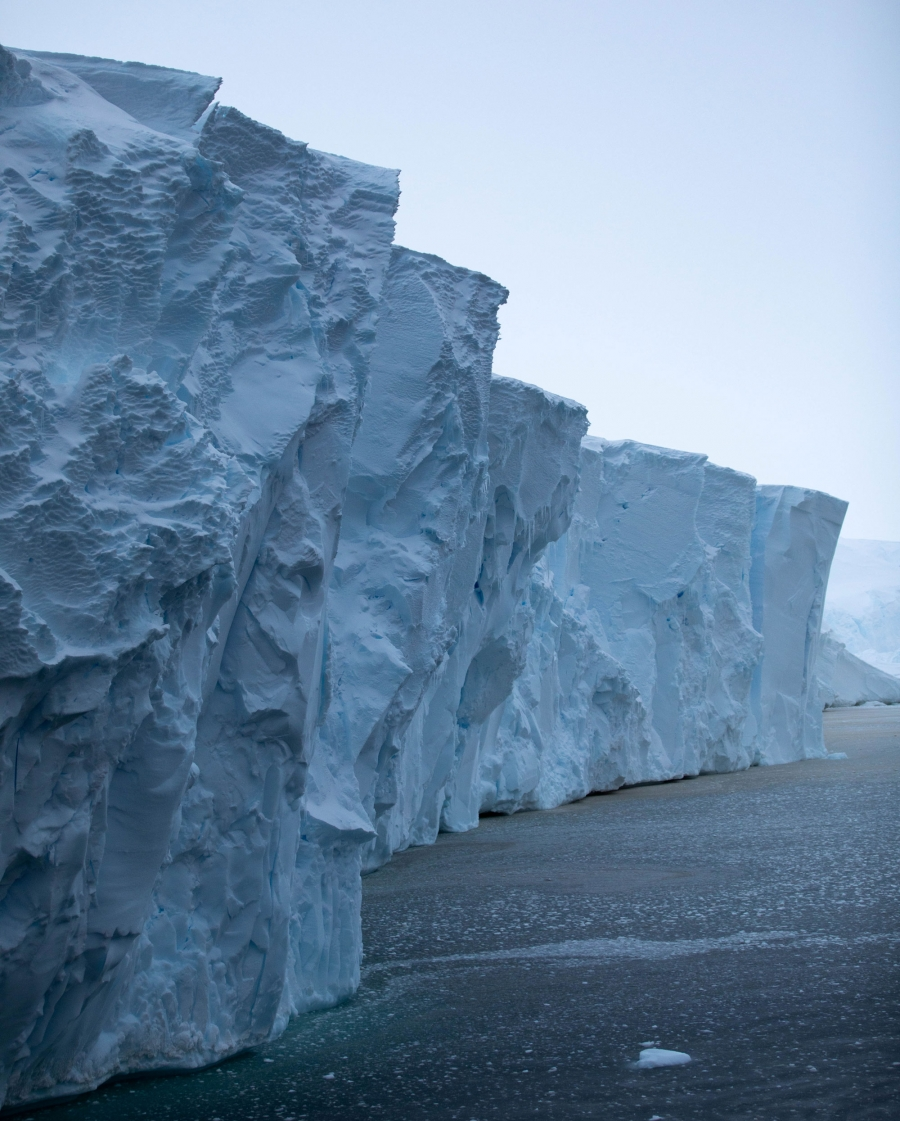 The front face of Thwaites glacier is shown rising an estimated 60 to 75 feet above the dark blue ocean waters.