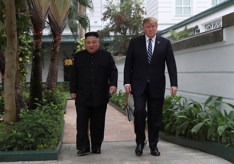 US President Donald Trump and North Korea's leader Kim Jong-un are shown walking side-by-side in a white-walled garden.