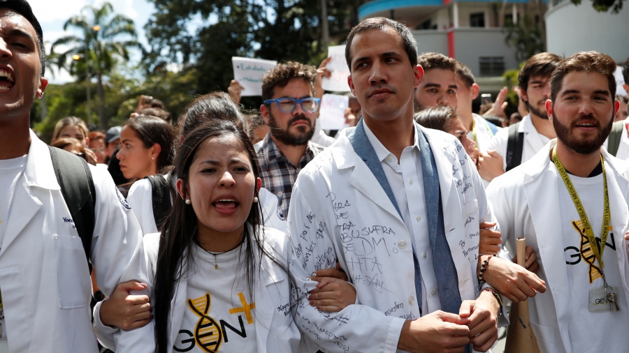 Protesters walk in white with interim President Juan Guaidó.
