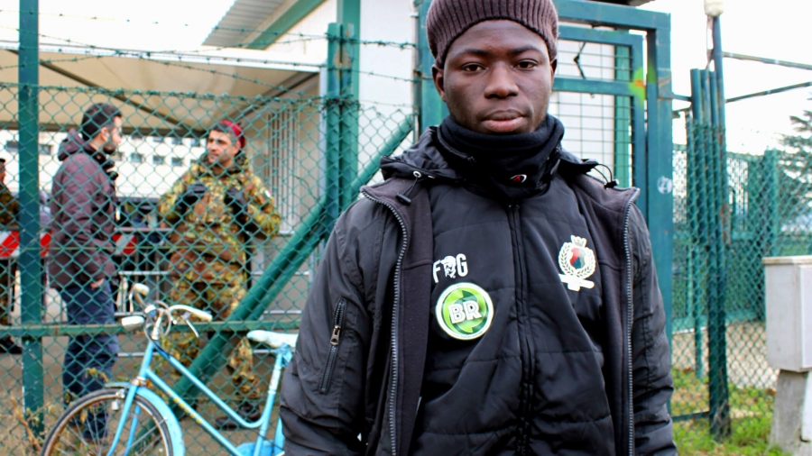 A young African man wears a green hat and a black jacket near a fence.