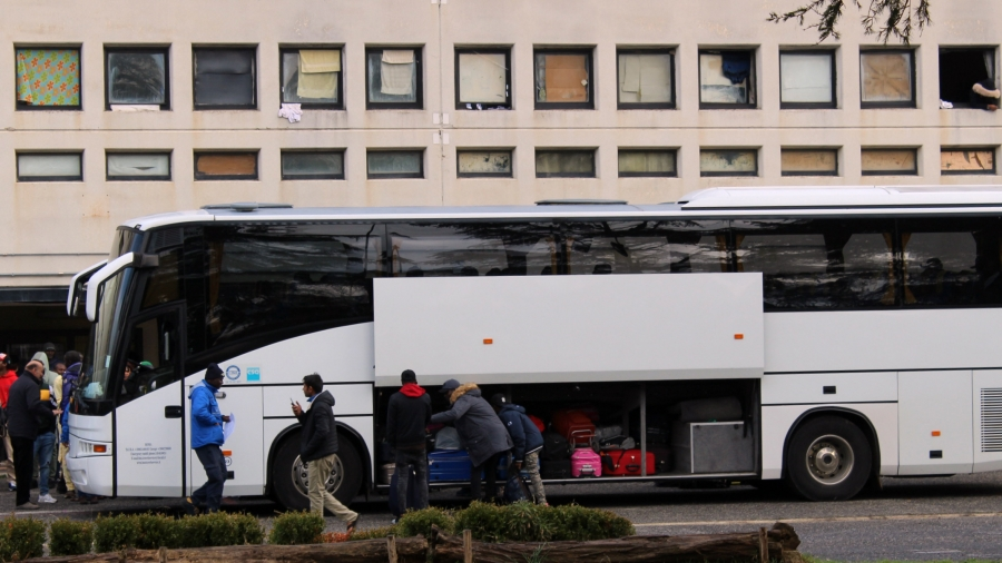 People load a white bus with luggage in front of a cement building.