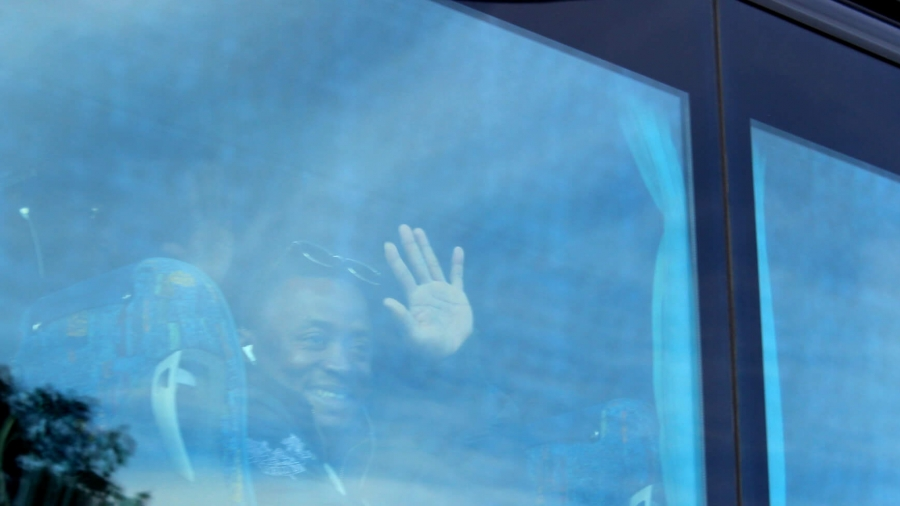 A young African man waves goodbye from the window on a bus.