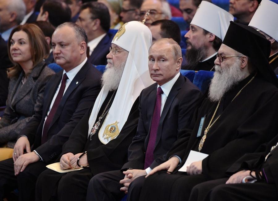Putin sits with head of heads of Orthodox church.