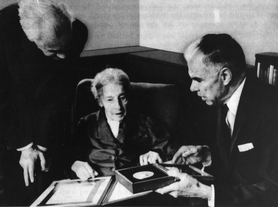 An elderly white woman sits between two white men presenting an award.