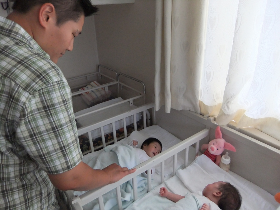 A woman stands over two cribs with babies in them.