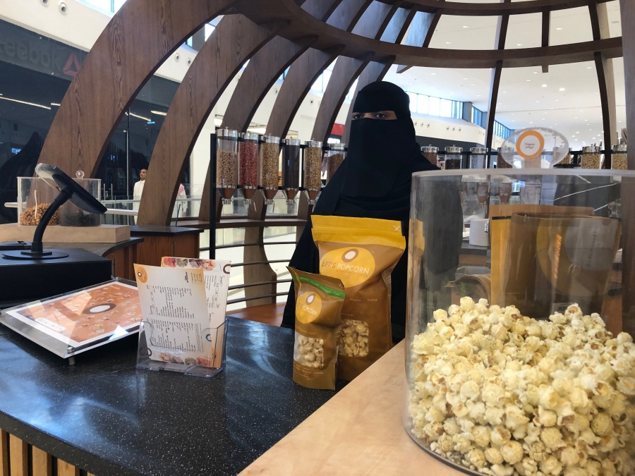 A woman wearing a black veil sells popcorn at a stand at a mall.