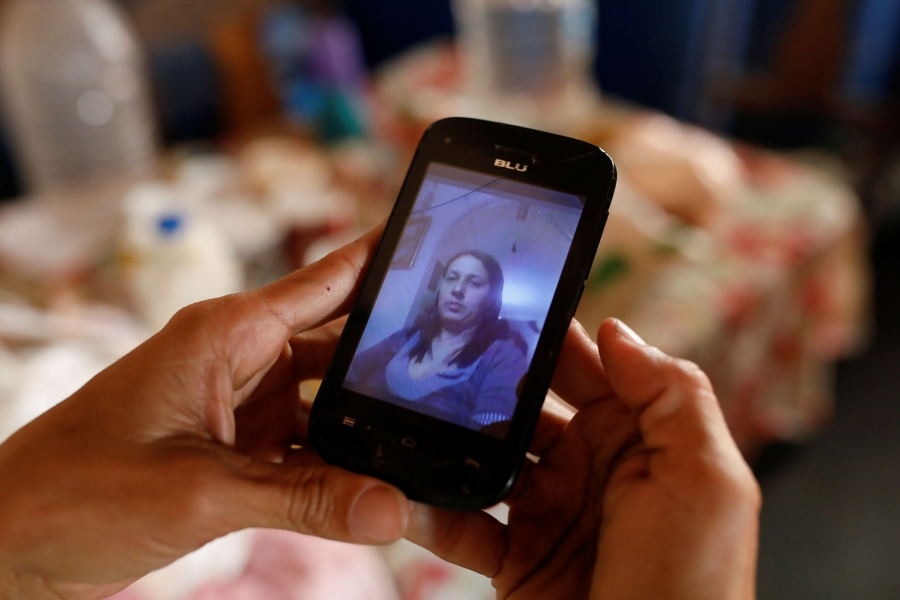 In a close-up photograph of a cell phone with a picture of Yaneidi Guzman on screen.