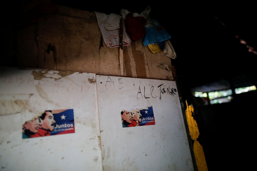 Two partially pulled off stickers are shown with the illustrated faces of Hugo Chavez and Nicolás Maduro.