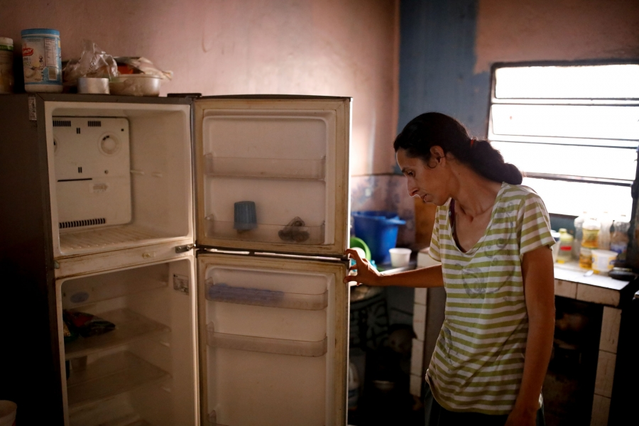 A woman is shown standing, opening up her empty refrigerator.