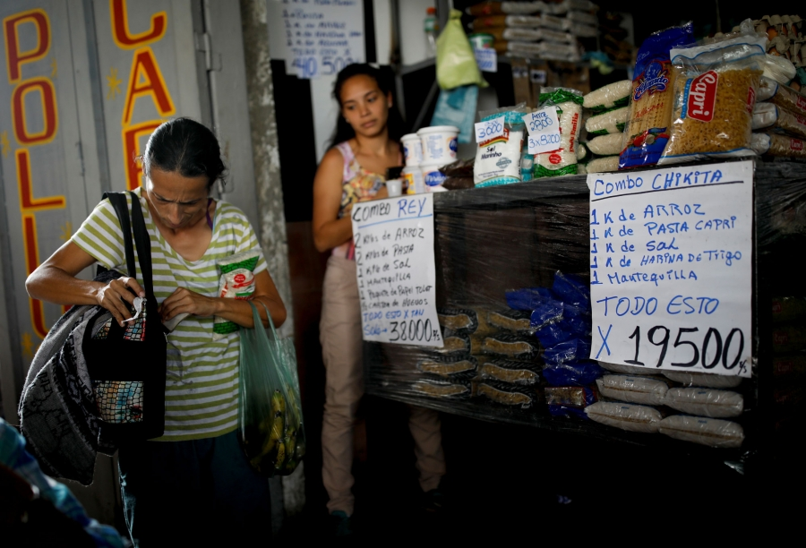 A woman is shown at a market with signs in Spanish for various groceries in front of her.