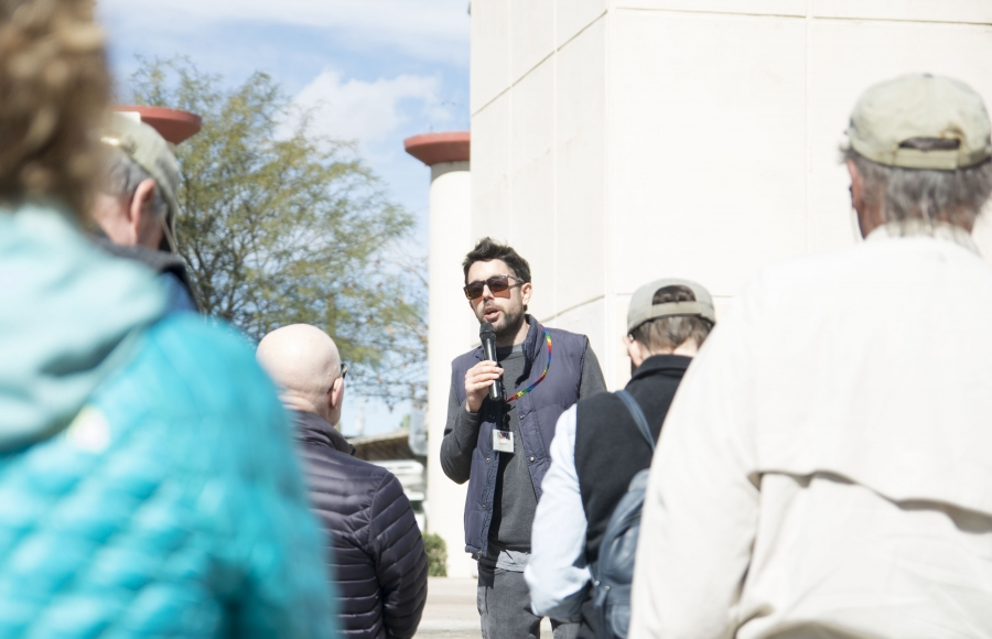 A man with a microphone talks to a small group