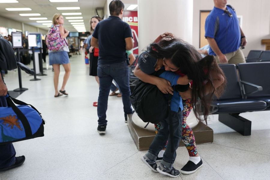 A mother hugs her son in the airport