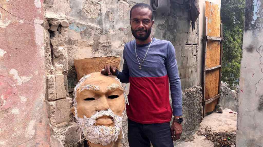 A man poses next to a large papier-mache mask