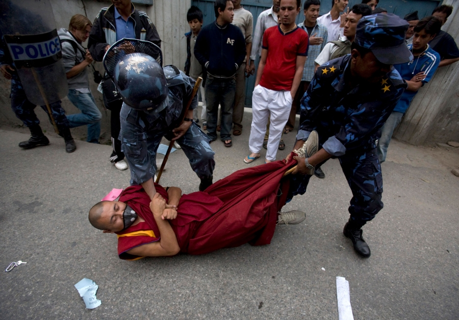 A monk is being dragged by police officers