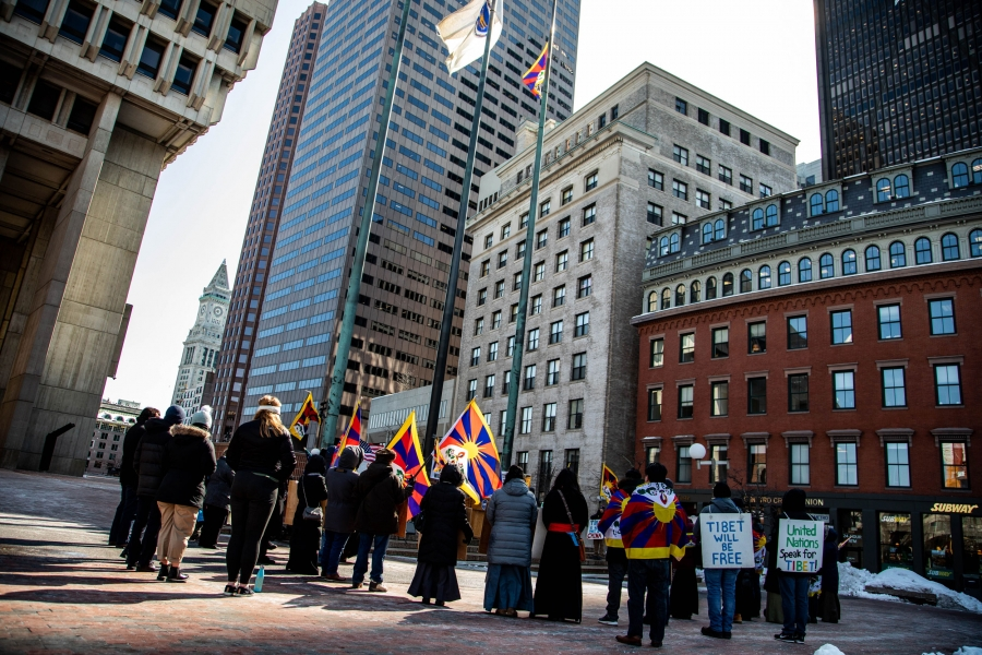 A group of people watch the Tibetan flag on a flagpole surrounded by the historic buildings of downtown Boston