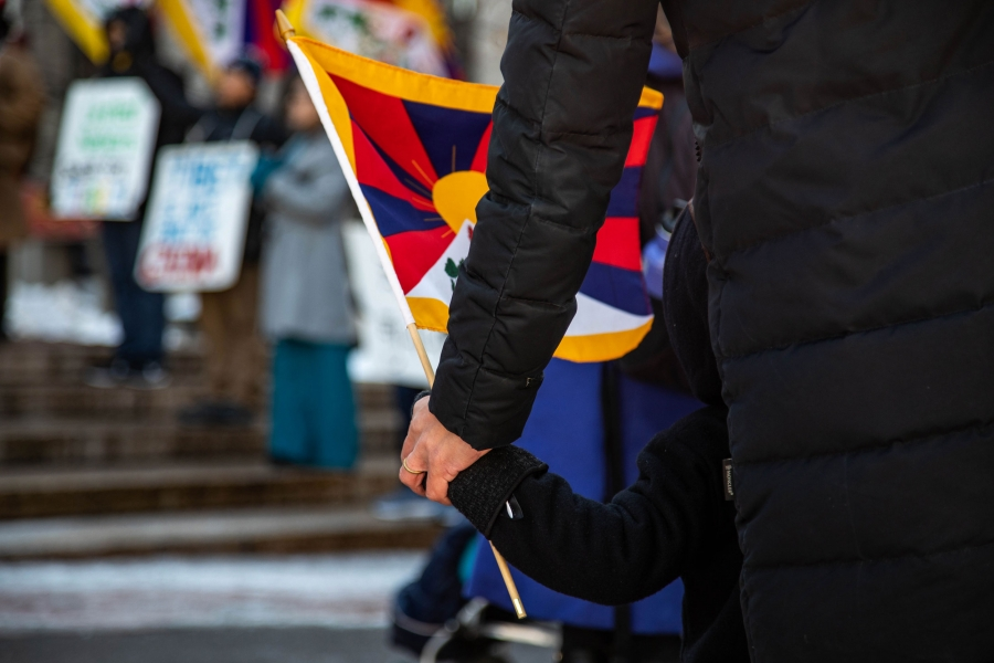 An adult holds a child's hand and a Tibetan flag