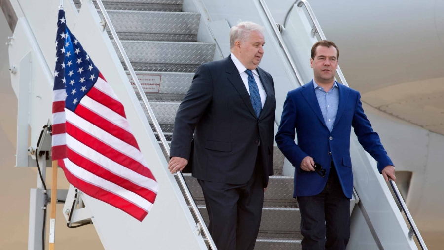 A man with white hair walks down the steps to a small plane with another younger man,