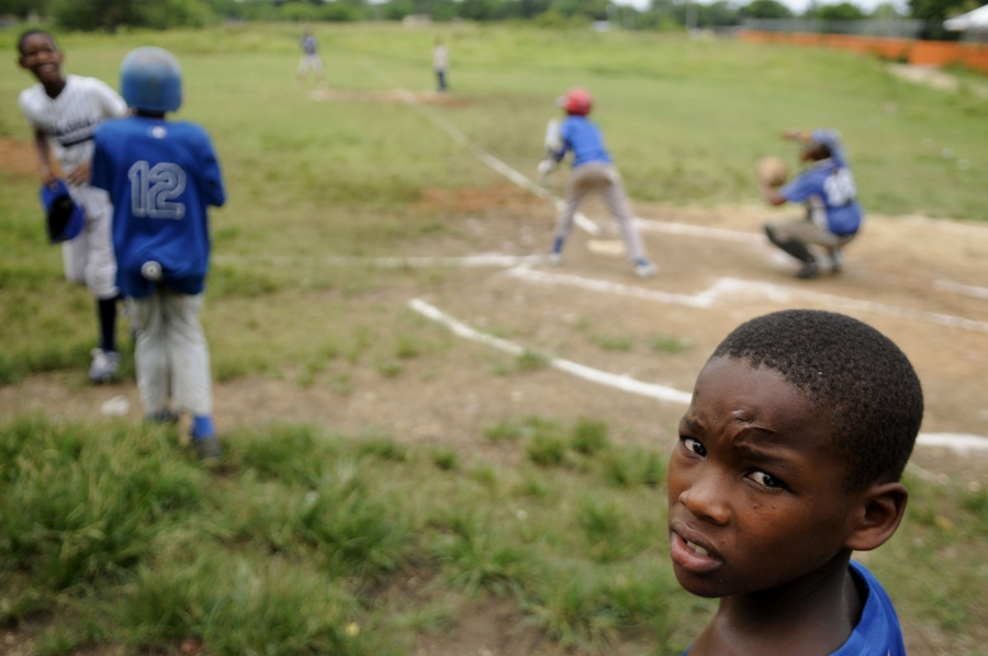 A young boy looks into a camera while others play baseball behind him