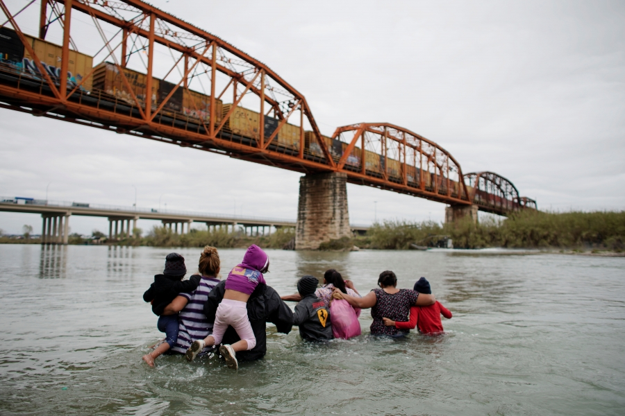 Migrants try to cross a river.