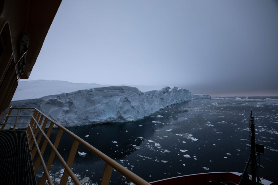 The railing of the Nathaniel B. Palmer is shown with Thwaites Glacier in the distance.