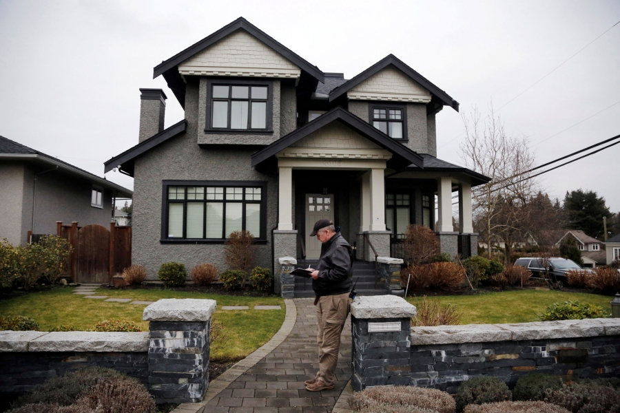 A member of a private security firm is shown stands outside of the family home of Huawei's financial chief Meng Wanzhou with a clipboard and a walkie talkie.