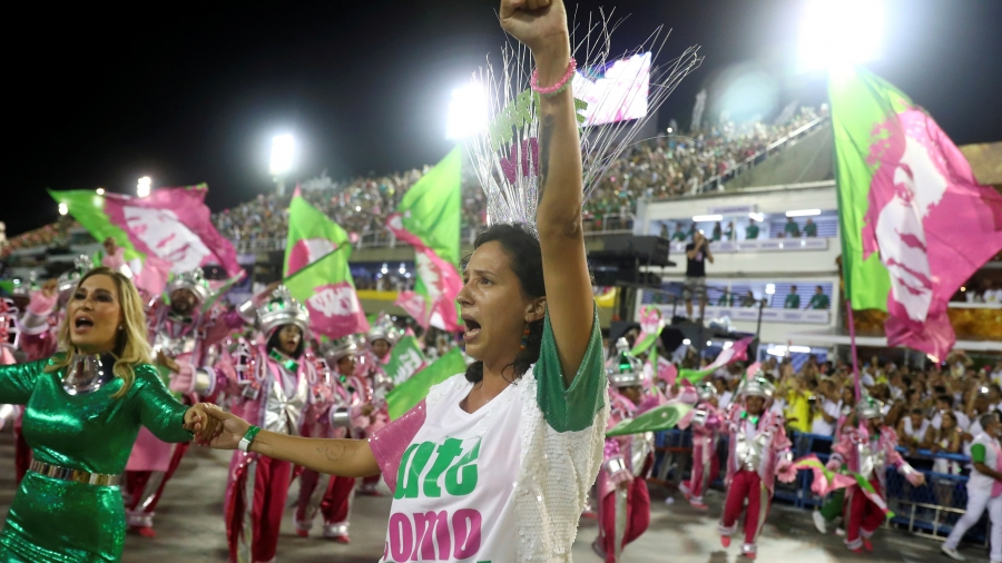 A woman raises her fist and shouts near a woman wearing dazzling green dress.