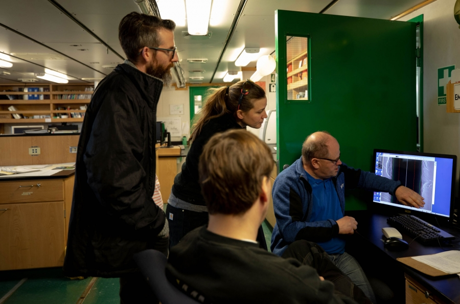 Scientists are shown tightly gathered around a computer.